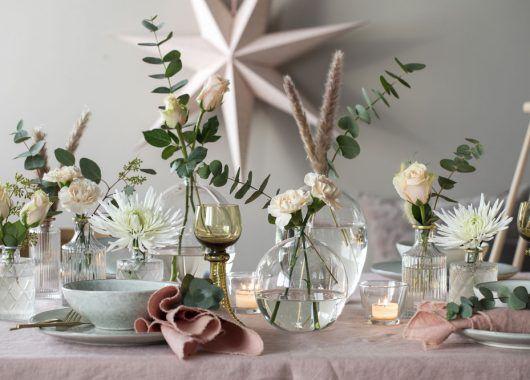 pyntet festbord med roser, krysantemum, nelliker, eukalyptus og strå