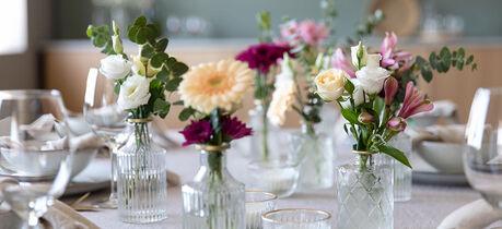 festbord pyntet med småvaser og blomster