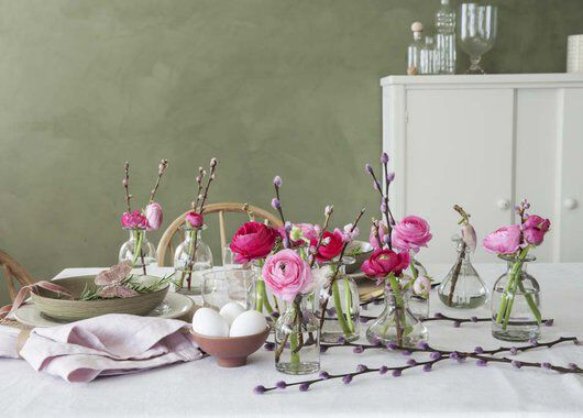 pynt bordet med ranunkler og gåsunger i mange små vaser