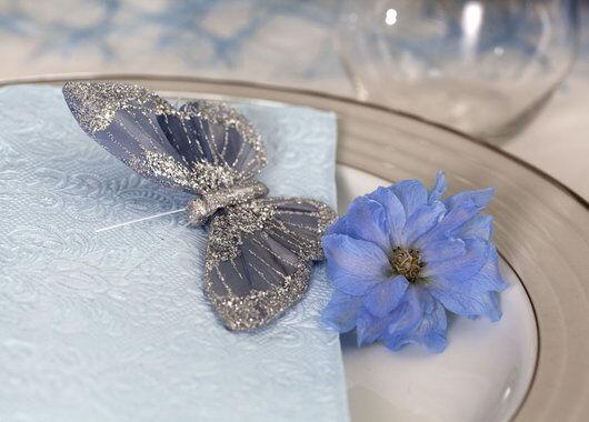 borddekorasjon med blå sommerfugl og blomst