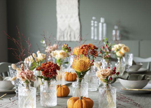 hyggelig pyntet høstbord med gresskar og blomster