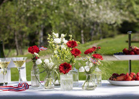 Pynt 17. mai-bordet med små vaser med blomster i nasjonalfargene