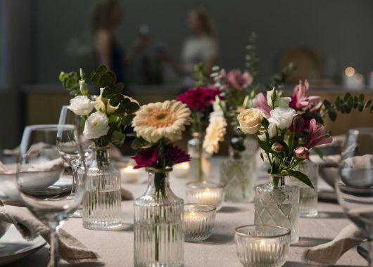 festbord pyntet med blomster i småvaser