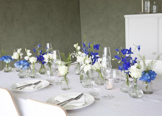 pyntet bord med blå og hvite blomster i små Dalebekken vaser