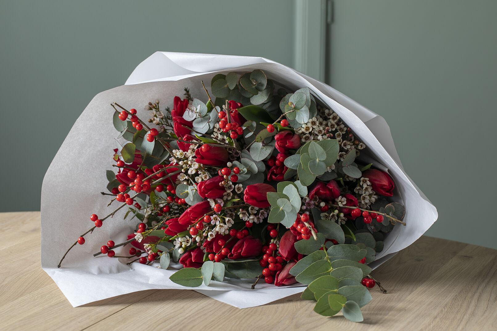 Røde tulipaner med grener i vase