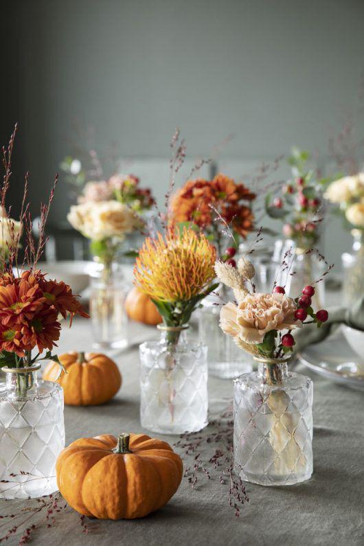 bordet pyntet med små pyntegresskar og blomster