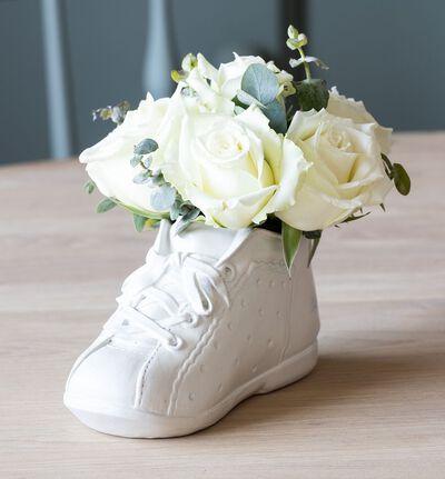 Hvite roser i babysko med bamse