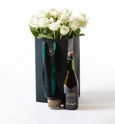Hvite roser i gavepose med bobler og sjokolade