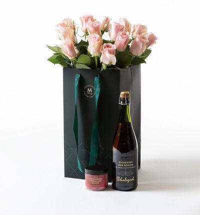 Rosa roser i gavepose med bobler og sjokolade
