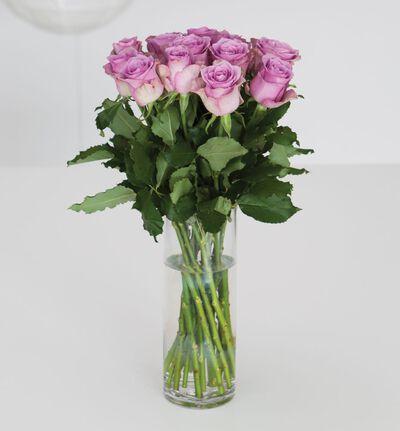 Lilla roser i gavepose med bobler og sjokolade