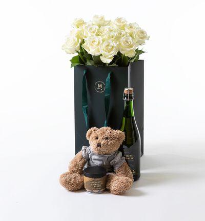 Hvite roser i gavepose med bamse gutt