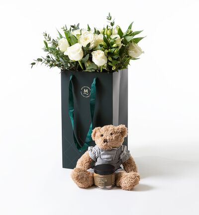 Hvit rosebukett i gavepose med bamse gutt